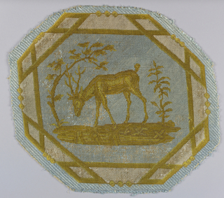"Octagonal medallion of upholstery fabric illustrating a fable by La Fontaine known as ""The Deer and the Vine"" or ""The Deer and his Antlers."" The pattern is in white and shades of yellow on a light blue ground."