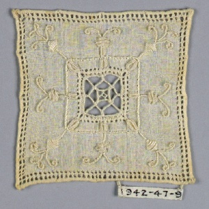 Square cover with cutwork center and embroidered leaf motifs.