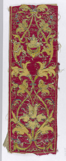 Fragments of an appliquéd and embroidered orphrey has symmetrical scrolling leaf and flowers forms of dark yellow on a red ground.