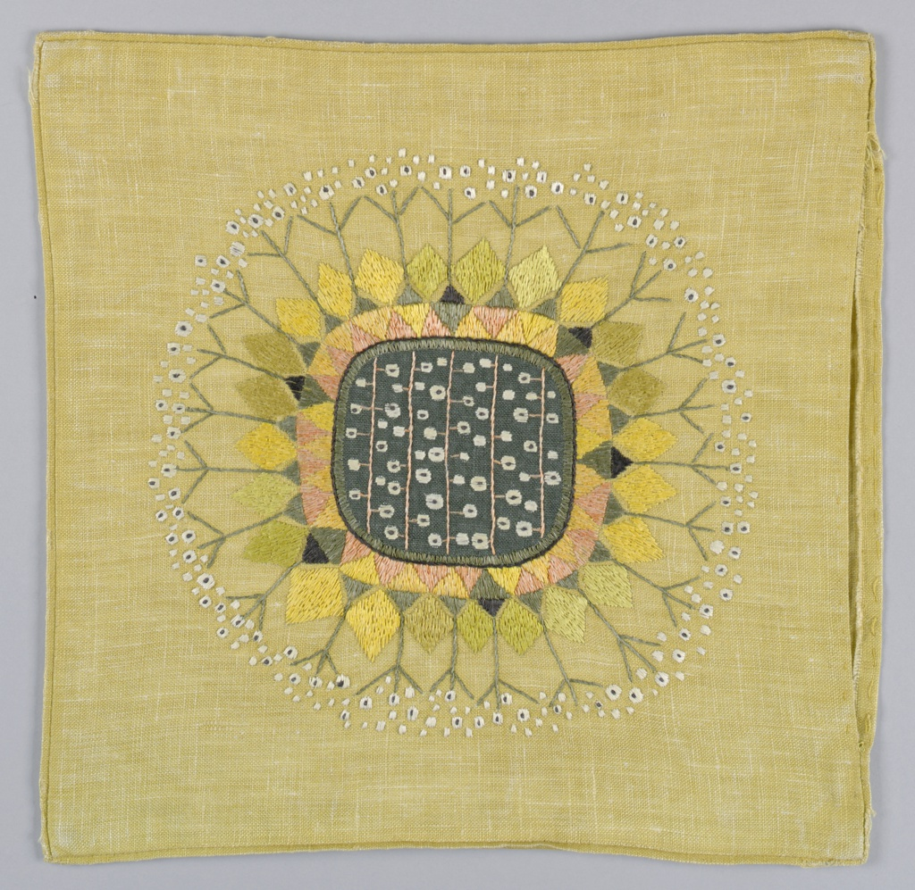Square pillow cover in a deep, cream-colored linen with a center panel of dark green. Embroidered in white and shades of yellow, pink and gray in a pattern of diamonds and stylized flower sprays.