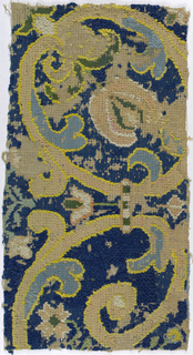 Fragment of an embroidered carpet with multicolored scrolling vine and leaf pattern.