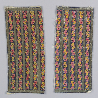 Pair of woven cotton cuffs embroidered with cotton and metallic yards in an alternating pattern of stripes and scrolls in yellow, red and blue.