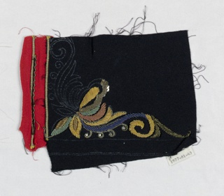 Black with attached red fabric has embroidered leaf motif.  Motif worked in gold, green, and blue colored coiled metal cord, gold sequins, rhinestones, and gold cord.  Chalk drawing on fabric continues the design.