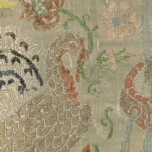 """Figured cream-colored silk brocaded in colored silks and chenille. In component """"a"""" the design shows a hunter, ship, bird on flowers, and a lion. For component """"b"""" the design in incomplete and shows a stag, peacock, flowers, and a fountain."""