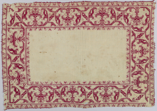 Rectangular table cover in a geometric floral pattern in red silk on linen.