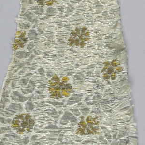 Pale blue-gray silk with closely spaced allover pattern of small conventionalized floral motifs in silver and gold. Extra weft of flat strips of silver appears on surface. Minute blossoms in gold, powdered over ground.