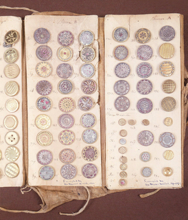 Sample book of buttons (1921-22-104/191) composed of five rectangular paper panels on woven fabric backing, four panels with rows of buttons made of gilded metal, foil, paillettes, or combinations of these materials. Paper panels with saleman's(?) headings and numbers written in ink; woven fabric backing with flap and ties. Fifth panel with numbered circular indentations where button were once mounted (buttons removed).