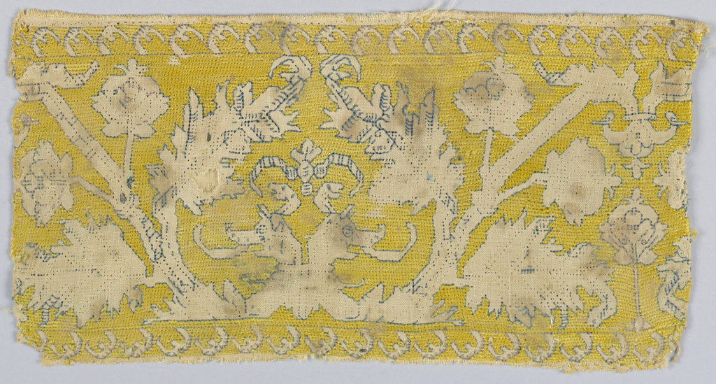 Textile fragment. Band showing symmetrical design of a double headed dragon and trees outlined in dark blue silk in reserve against a yellow embroidered background.