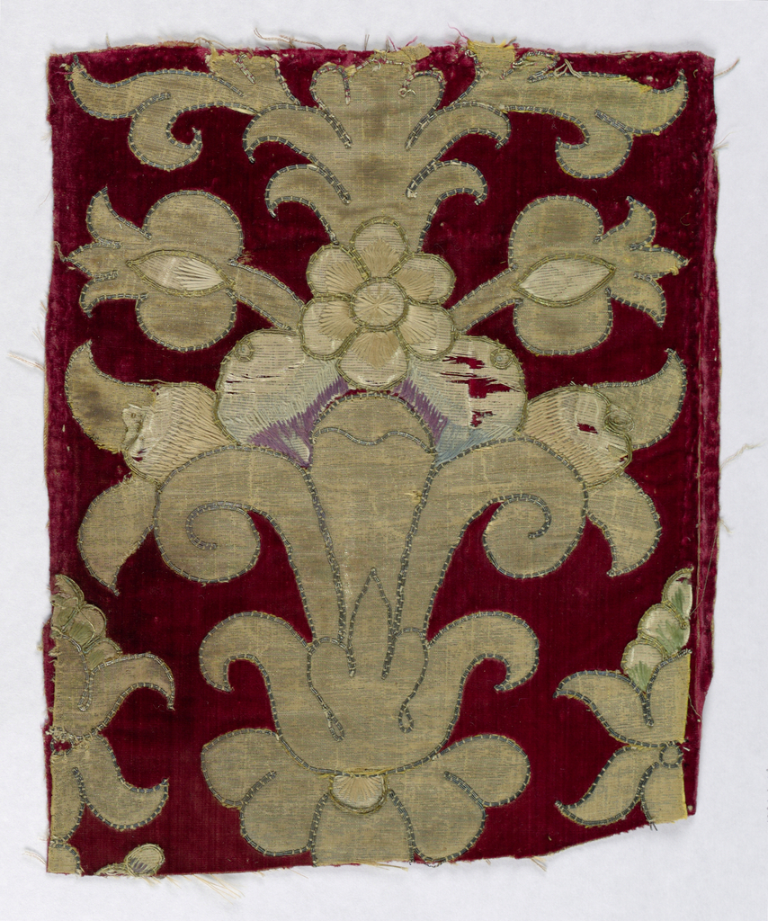 Appliqué with vase and pomegranate motifs on red velvet ground. Couching with metal thread. Embroidery in colored silks. Textile is a fragment of a larger piece.
