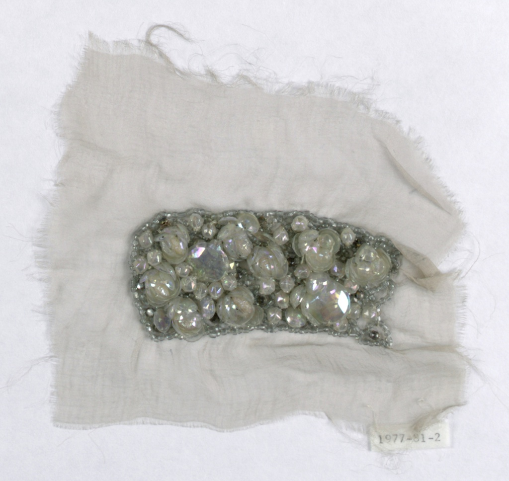 Small sample of white silk with a densely beaded band, with clear glass beads and  transluscent, faceted sequins.
