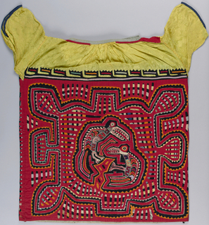 Woman's blouse with cut-out cottons in many colors, with red predominating, stitched in reverse-appliqué technique to make a design of long-beaked birds within a labyrinth of abstract shapes. This forms body of the blouse, with slightly different patterns front and back, and is sewn into yoke of patterned yellow rayon to form a short-sleeved blouse with a gathered neckline, with red appliqué at the shoulder seam.