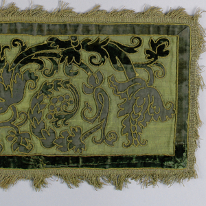 Green panel of green velvet applique and olive green couching in formal curving vine design on a green background. Border of green velvet, trimmed with gold fringe. Lined in green silk.