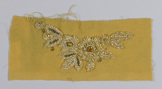 Mustard yellow fabric with embroidered flower and leaf motif worked in gold beads, large yellow rhinestones, gold sequins, and faux pearls.
