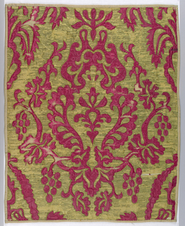 Foundation of red silk damask with applique of gold metal cloth. Symmetrical design of central palmette with flanking foliage and berries. Backed with cotton.