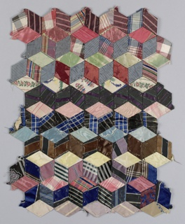"Fragment of a quilt top in ""Tumbling Blocks"" pattern, made from small diamond shapes stitched together to create the illusion of cubes. The woven pieces are in silk stripes, plaids and a few small floral patterns."