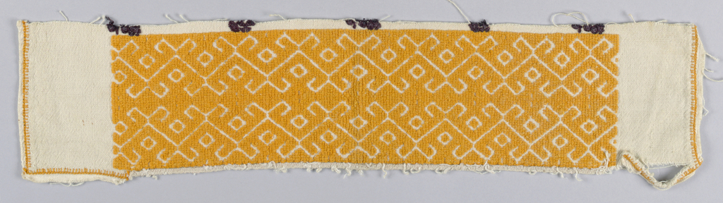 Band solidly embroidered with yellow-orange cotton in a simple geometric pattern. The border has been cut from a blouse on which there are traces of black embroidery.