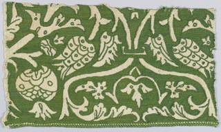 Pattern of tulips, pomegranates and Turkish-like floral forms in reserve against a green silk embroidered background.