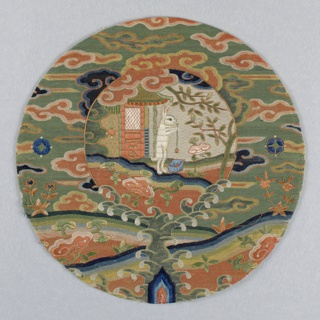 Circular medallion with a frame and a pictorial center. The frame contains a landscape with cloud motifs embroidered in polychrome silks on a green ground. In the center, a white rabbit is standing in front of small building with trees, stirring a blue vessel with a long spoon. The rabbit beating the elixir of life is often shown on the robe of a T'aoist priest.