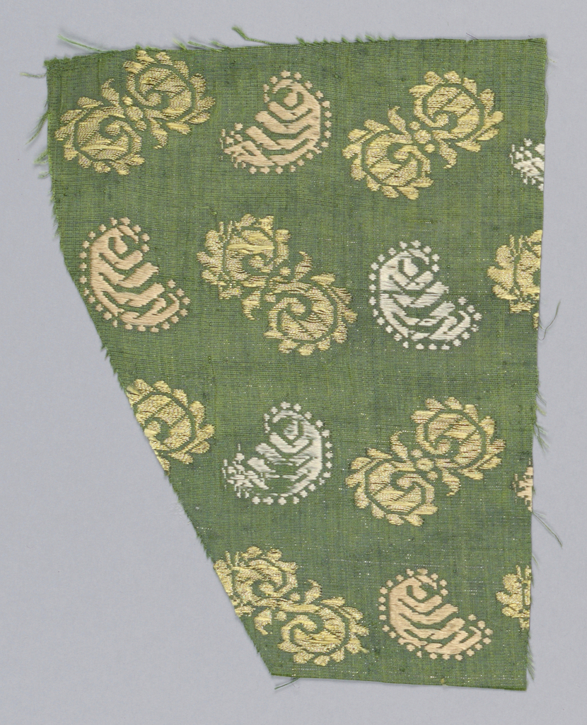 Green silk ground with an extra weft of silver. Design in rows of two units alternating and changing directions in each row. One motif is an 'S' form; the other a 'C'. The 'S' is in yellow with metal thread; the 'C'  is alternately white and peach.