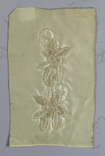 White ground with embroidered floral pattern worked in white irridescent seed and bugle beads and faux pearls.