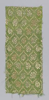Greenish-yellow silk with a small-scale lattice framework enclosing a single leaf-like form.
