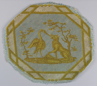 "Octagonal medallion of upholstery fabric illustrating a fable by Aesop known as ""The Fox and the Crow."" The pattern is in white and shades of yellow on a light blue ground."