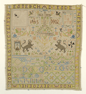 Sampler densely embroidered with geometric and floral pattern bands and spot motifs including religious and heraldic motifs, within a frame of text.