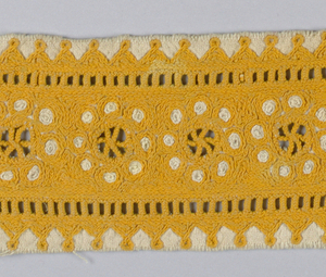 Fragment of a sleeve embroidered in yellow-orange on white cotton. Circular wheel pattern with cutwork pattern in center.