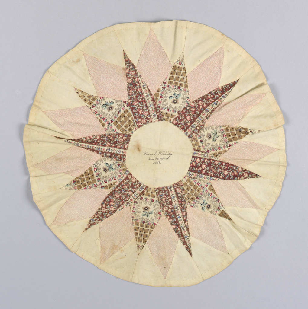 "Patchwork medallion with a star pattern in unbleached cotton and three roller-printed cottons in browns, tans and pinks. Handwritten in dark brown ink in the center circle; ""Olivia C. Whitridge, New Bedford, 1853"""