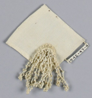 Tassel attached to an embroidered ring near the corner of a small square of fabric.