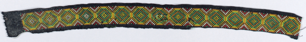 Narrow geometrical border embroidered in red, white, yellow, orange, and green ramie cross-stitch on old black traders' cotton