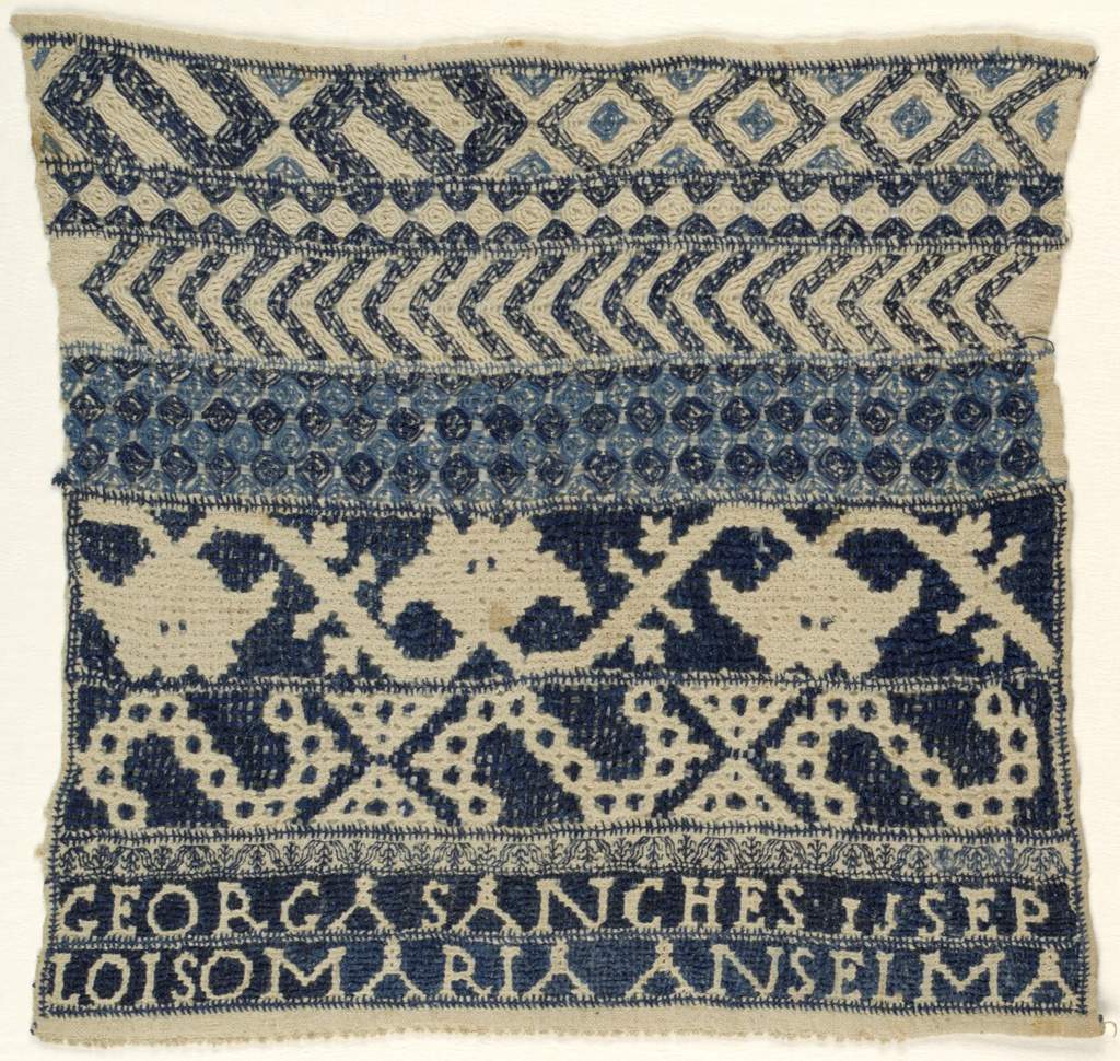 Bands of pattern in blue and white. Needle lace at bottom edge.