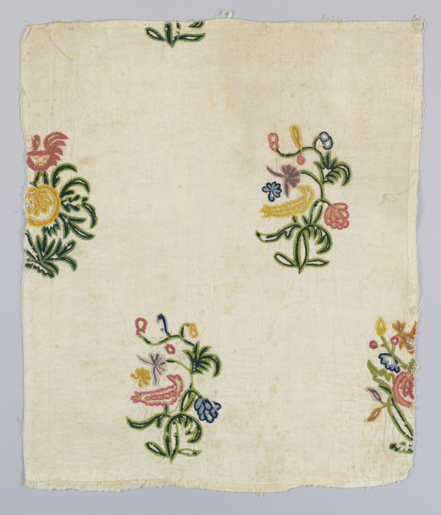 Multi-colored crewel embroidery on ivory cotton, spaced alternating rows of two motifs of a bird in a flowering tree.