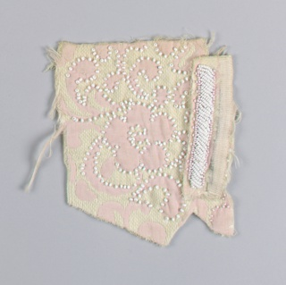 Off-white with woven pink floral motif outlined with white seed beads. Another sample of same fabric is pinned to this sample, with a band of white and pink seed beads.