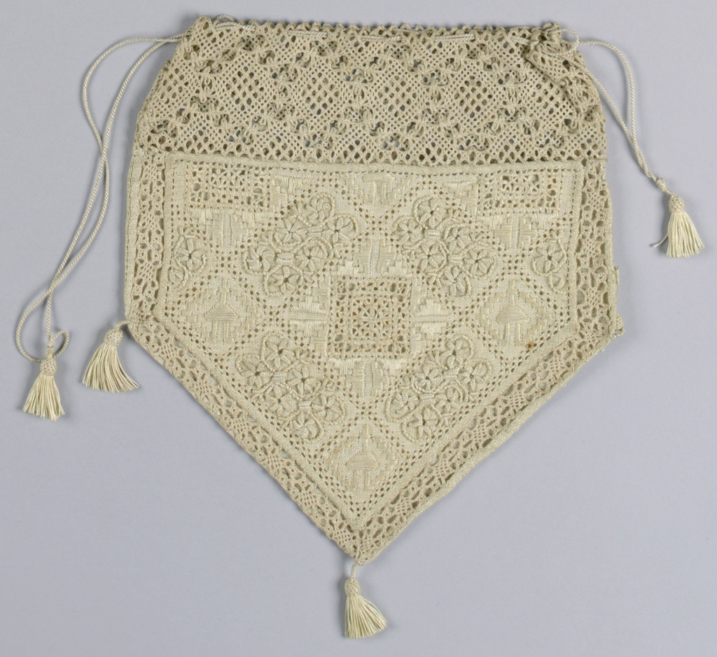 A five-sided bag has a band of bobbin lace at the top and a drawstring closure. Below is a panel of linen decorated with cutwork and embroidery and a narrow band of bobbin lace. The back is plain weave and small tassels adorn the three lower corners and the drawstring.