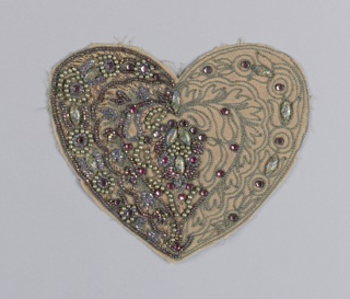Beige fabric cut in a heart shape with incomplete decorative motif. Embroidery worked in gold and purple beads, pink and purple rhinestones, copper metal thread, and multicolored confetti glass jewels.  Edges outlined in blue cord couched in metal thread.