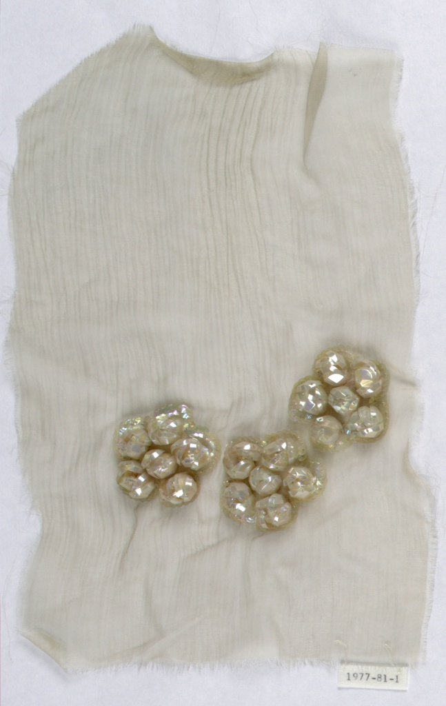 Small sample of white silk embroidered with three flowers made up of clusters of faceted, transluscent sequins.