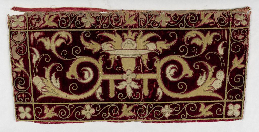 Symmetrical scrolls in gold on cut velvet in red.