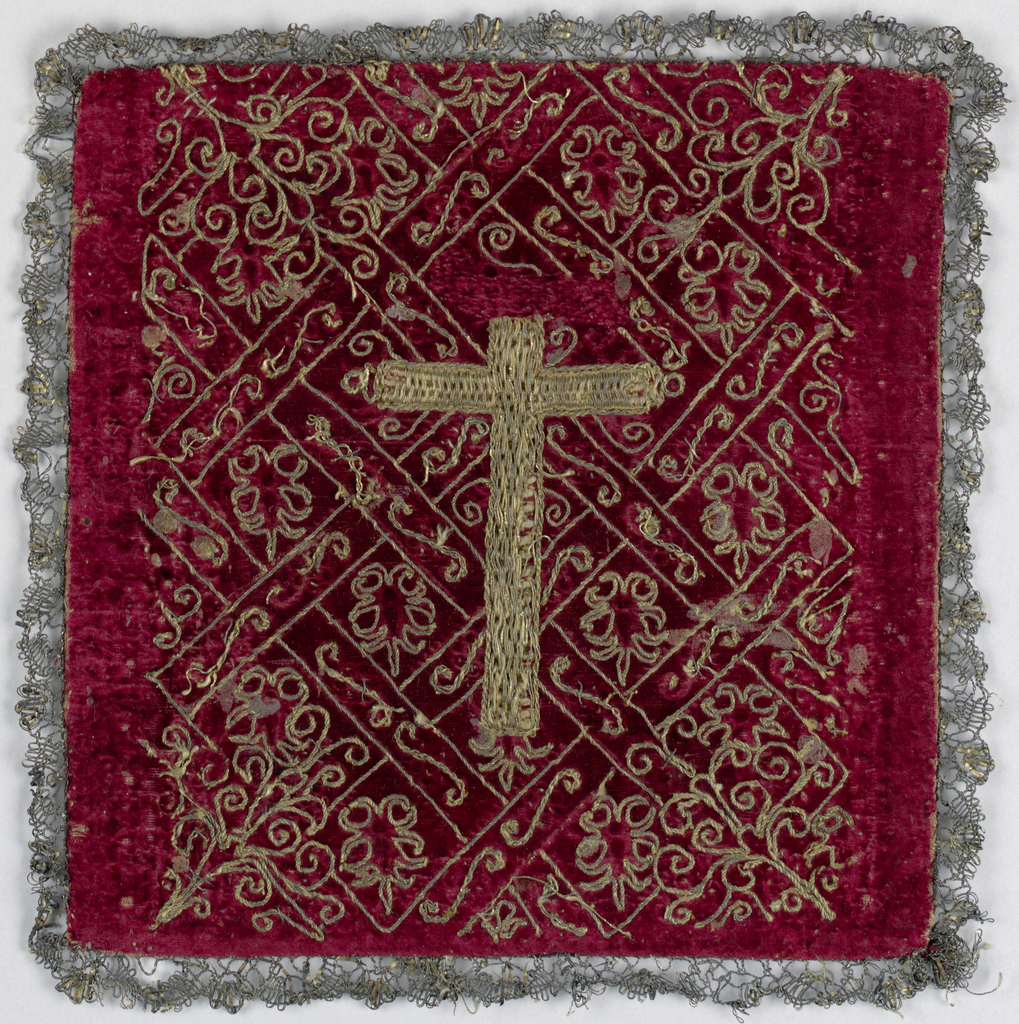 Small square of red velvet, embroidered in gold in all-over pattern of interlacing geometric design, with foliage forms in spaces, and corner designs of foliage all highly stylized. Cross in center, gold thread worked over cord to give relief. Trimmed with narrow gold lace. Backed with dark green plain raw silk (probably Spanish) of later date, 18th century, than embroidery.