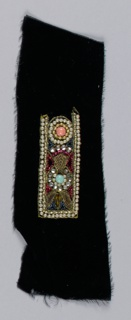 Black velvet embroidered with a rectangle outlined in faux pearls, containing gold metal cord and multicolored beads and rhinestones.