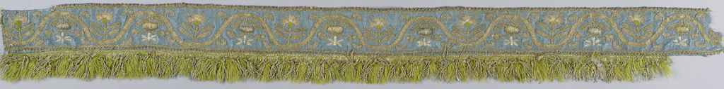 Narrow border of blue silk embroidered in gold, silver and pale tints of silk. Design is a curving vine with a symmetrical arrangement of small carnation in profile. Trimmed with very narrow metal edging on top and bottom. Bottom has a fringe of green silk and gold thread.