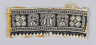 Fragment of sleeve decoration with black embroidery on white linen. Small geometric design between dotted edges. Tooth design on one side.