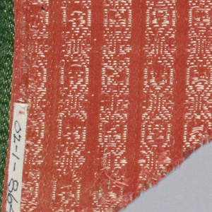 Deep scrolling border on red satin fabric with patterned white stripes.