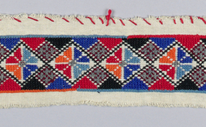 White cotton embroidered in a multi-colored geometric pattern of orange, dark blue, light blue, red, and grey.