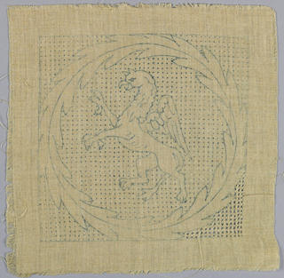 Partly worked pattern of a griffin in a laurel wreath.