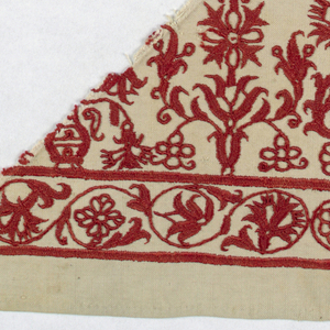 Cotton embroidered in red silk. Two horizontal lines creating a border for scrolling linework and florals. Repeat pattern of florals above border.