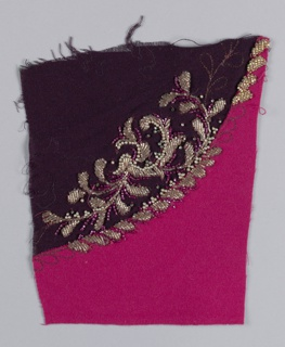 Pieced fuschia and burgandy fabrics with embroidery worked at the join. The incomplete floral motif is worked in gold and fuschia seed beads, faux pearls, and rhinestones. Motif is outlined with row of chain stitch worked in metal thread.