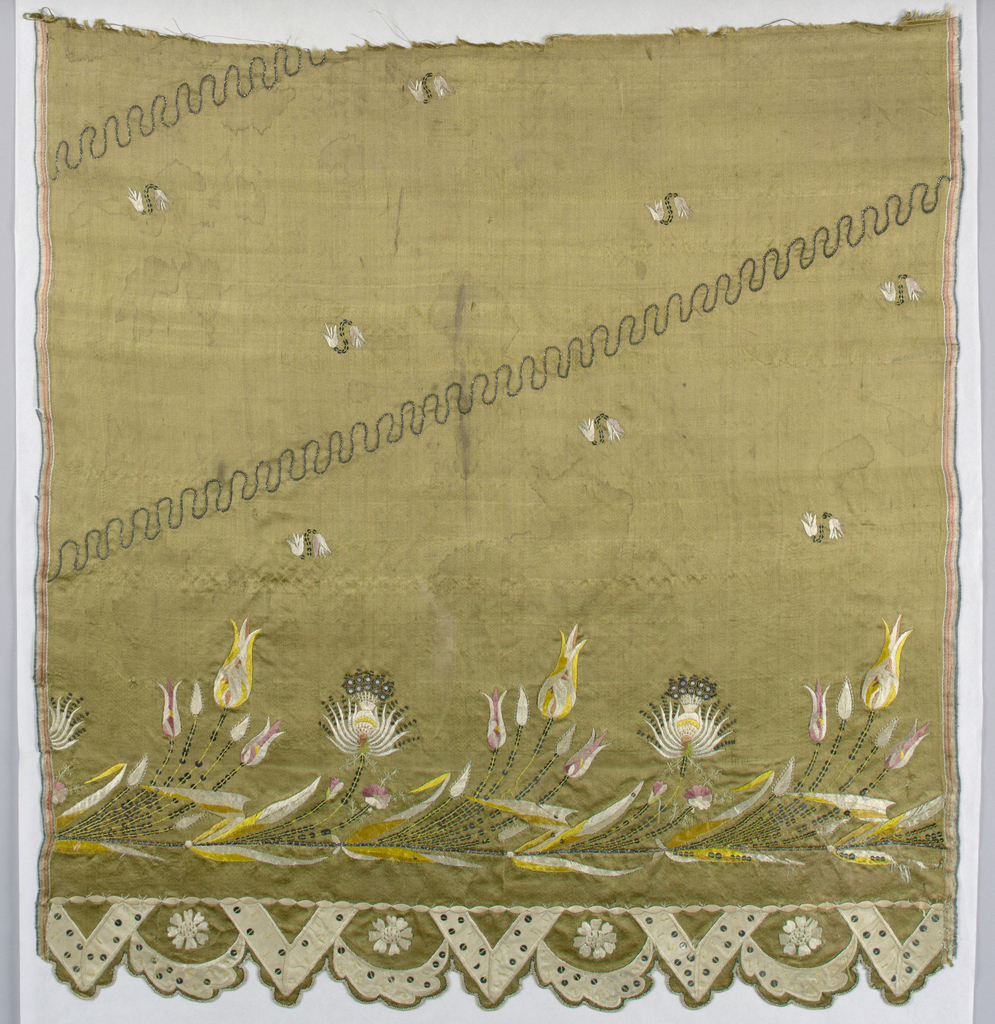 Lower part of a light brown satin skirt panel with a scalloped bottom edge accentuated by daisy-like flowers, arcs and V-shapes of applied white satin sprinkled with sequins. Band of stylized flowers above in white and multicolored silks, metal thread, purls and sequins. Remainder decorated with widely spaced pairs of tiny flowers. Serpentining diagonals in chain stitch.