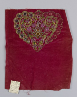 Red velvet fabric embroidered in a partially completed, heart-shaped motif worked in purple seed beads, gold bugle and round beads, green, orange and purple rhinestones and fuschia colored metal thread in a boullion stitch.