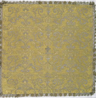 Golden yellow ground of warp twill with small symmetrical arabesque pattern in the same color in a weft twill. Arabesques are outlined and embellished with couched silver threads to form a continuous allover pattern. Small cross in the center of silver couched in black. Edged with narrow gold bobbin lace and lined in fine blue ribbed silk.